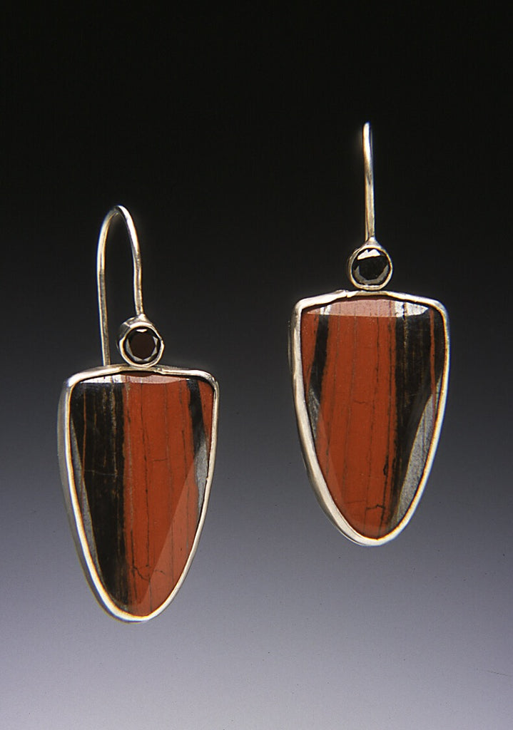 Tube set black diamonds perched above bezel set jasper hematite dangle earrings.