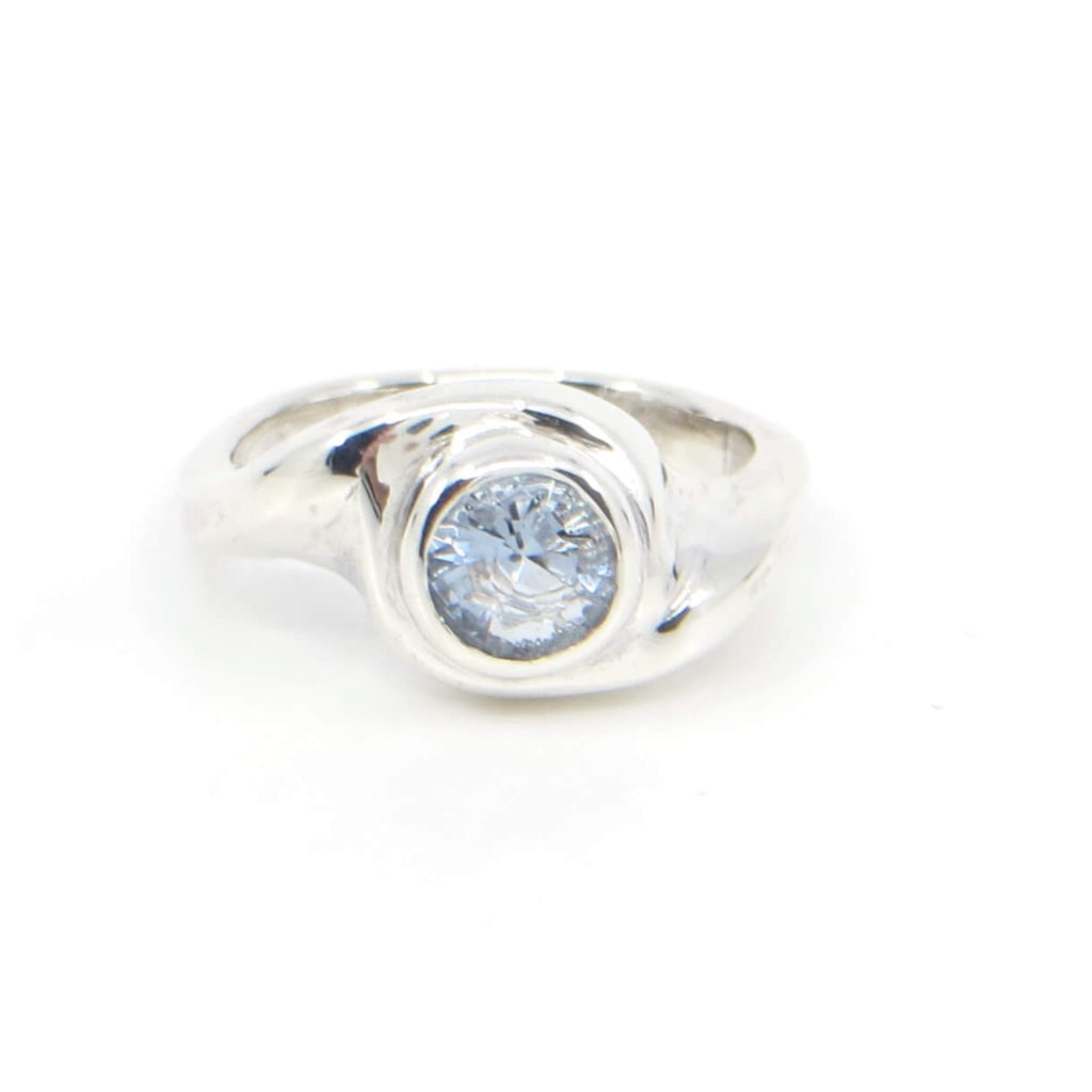 Curvilinear sterling silver ring with 6mm sparkling light blue topaz. US Size 6-6.25