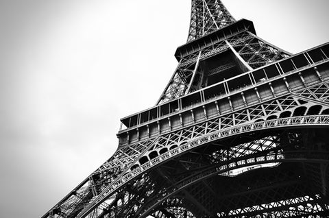 A black and white image of the Eiffel Tower in Paris from the ground.