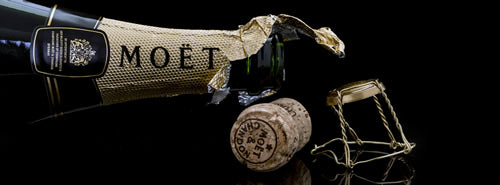 An open bottle of Moet & Chandon with a cork to the side.