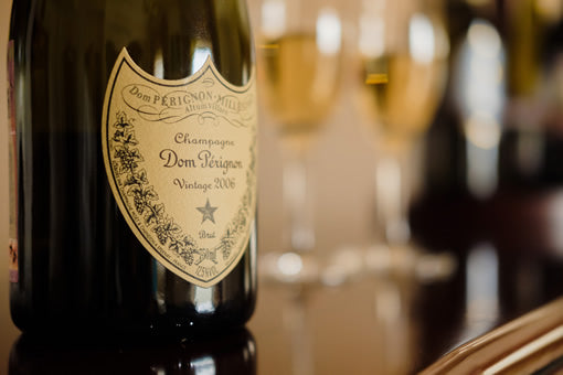 A bottle of Dom Perignon with champagne glasses in the background.