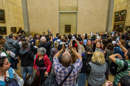 "Tourists crowd the ""Mona Lisa room"" at the Louvre museum in Paris, France."