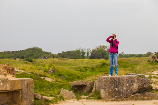 A tourist taking a photo at Pointe du Hoc in Normandy, France.