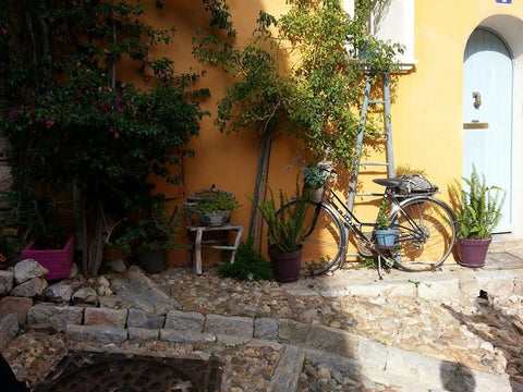 An old bike on a yellow house in Provence, France.