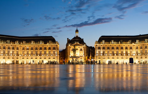The illuminated Place de la Bourse in Bordeaux in the early evening.