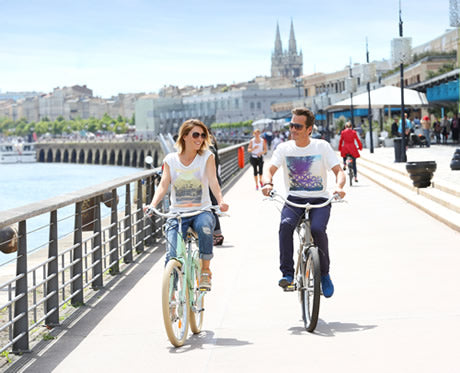 A couple ride their bikes along the Bordeaux riverfront path.