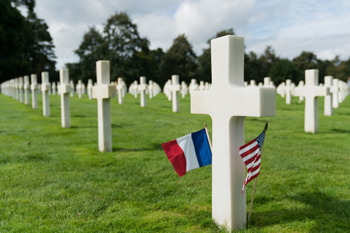An American and French flag mark the gravestone of an American soldier at the U.S. cemetery at Colleville-Sur-Mer in Normandy, France