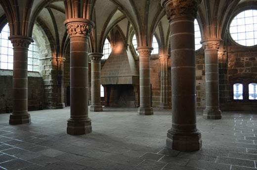 A row of columns and ancient fireplace inside of Mont Saint Michel abbey.