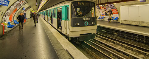 Two people walk along the subway platform in Paris as the metro departs the station.
