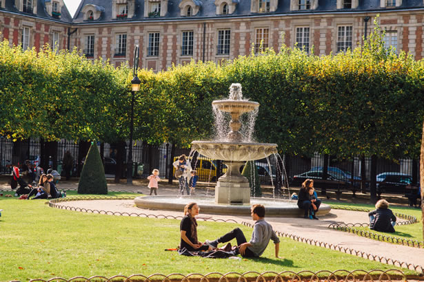 People sitting on the lawn in the middle of the Place des Vosges.