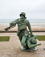Load image into Gallery viewer, A statue at Omaha Beach depicting a soldier saving a comrade.
