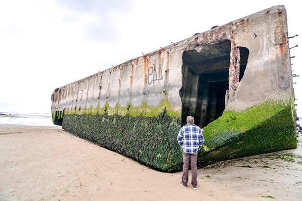 "A man stands in front of a ""Mulberry"" at the artificial harbor at Arromanches."