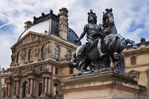 A statue of a French king riding a horse outside of the Louvre in Paris.