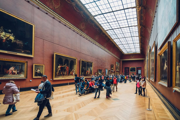 Tourists admiring some renaissance era paintings in the Louvre museum.