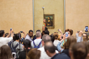 Tourists taking selfies in front of the Mona Lisa.
