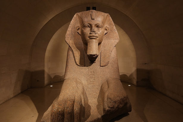 A large Egyptian statue inside the Louvre.