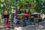 Load image into Gallery viewer, A cafe in a treelined square in Arles, France.