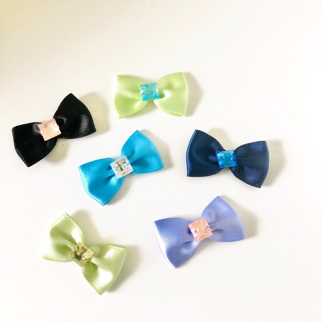 Single square Gemstones of different colors on satin bows in several colors