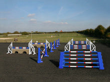Load image into Gallery viewer, Photograph of the PolyJumps Advanced set in an arena. The set's contents are as follows: 1 set of Combi Blocks, 4 sets of Cross Wings and 3 sets of 8 Cups with 4 Bridge Fillers and 21 Poles. This set's colour scheme is primarily Blue.