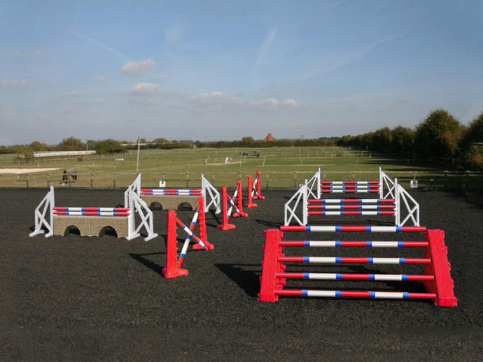 Photograph of the PolyJumps Advanced set in an arena. The set's contents are as follows: 1 set of Combi Blocks, 4 sets of Cross Wings and 3 sets of 8 Cups with 4 Bridge Fillers and 21 Poles. This set's colour scheme is primarily Red.