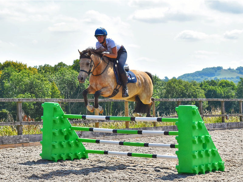 Horse and rider jumping over a pair of Eco Green Combi Blocks with 4 9 Band Practice Poles.