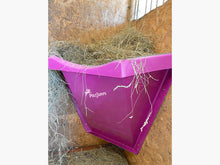 Load image into Gallery viewer, Pink Hay Feeder attached to wall inside stables.