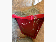 Load image into Gallery viewer, Red Hay Feeder attached to wall inside stables.