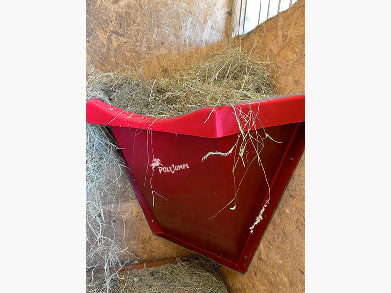 Red Hay Feeder attached to wall inside stables.