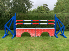 Load image into Gallery viewer, Photograph of a pair of Blue Cross Wings with 2 9 Band Practice Poles coloured: Red, Blue & White. Underneath the poles sit 2 White Bridge Fillers with Red Brick Graphics on them.