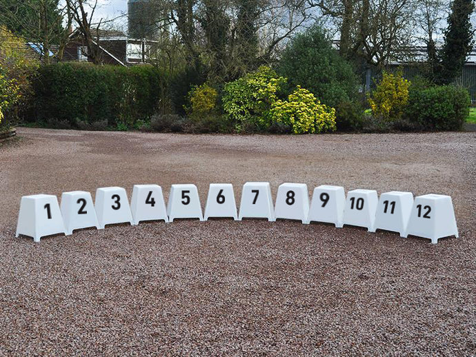 Show Jump Markers, numbers 1 to 12, sat on gravel displaying scratch resistant painted letters.
