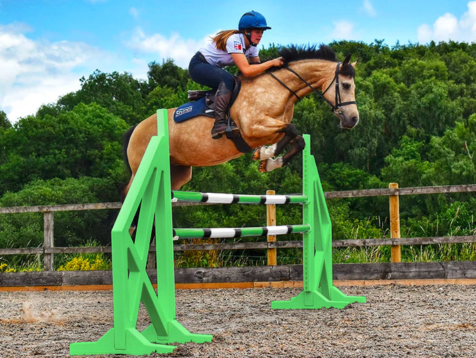 Horse and rider jumping over a pair of Eco Green Cross Wings with 2 9 Band Practice Poles.