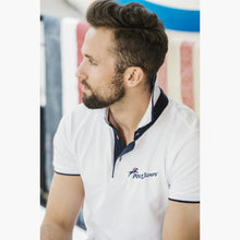 Load image into Gallery viewer, Model wearing White Poloshirt, raised collar revealing Navy Blue contrast fabric. PolyJumps Logo on wearer's left chest.
