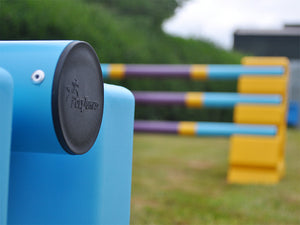 Close up photograph of the end cap on a practice pole. PolyJump Logo embossed onto the cap.