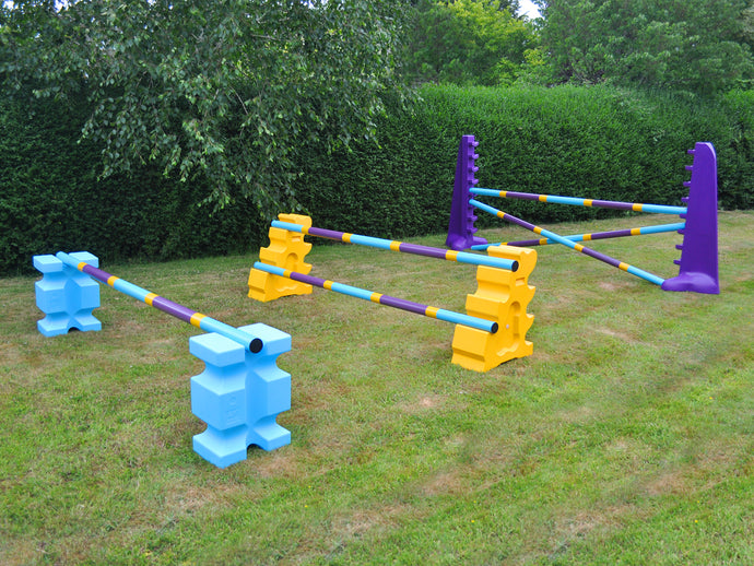 Photograph of the Club Jump Set. From left to right, 1 pair of Baby Blue PolyJump Block holding 1 9 Band Practice Pole: Club Style. 1 pair of Yellow MultiJumps holding 2 9 Band Practice Poles: Club Style. 1 pair of Purple 8 Cups holding 3 9 Band Practice Poles: Club Style.