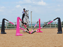 Load image into Gallery viewer, Horse and rider jumping over the middle of the PolyJumps Spider Set; comprised of 2 pairs of 8 Cups, one Black the other Pink with 4 9 Band Pro Poles. Alternate colouring: Pink, White & Black and, Black, White & Pink.