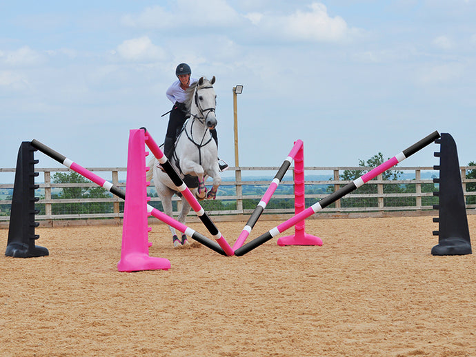 Horse and rider jumping over the middle of the PolyJumps Spider Set; comprised of 2 pairs of 8 Cups, one Black the other Pink with 4 9 Band Pro Poles. Alternate colouring: Pink, White & Black and, Black, White & Pink.