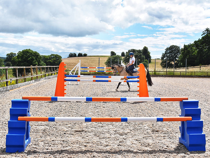 Blue MultiJumps with 9 Band Poles coloured Orange, Blue and White. Behind that, 2 orange 8 Cups with 9 band poles coloured: Blue, Orange and white. At the back White Cross wings with 9 band poles coloured Blue, white and orange. All jumps in arena with horse and rider walking between jump sets.