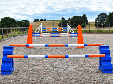 Load image into Gallery viewer, Blue MultiJumps with 9 Band Poles coloured Orange, Blue and White. Behind that, 2 orange 8 Cups with 9 band poles coloured: Blue, Orange and white. At the back White Cross wings with 9 band poles coloured Blue, white and orange. All jumps in arena.