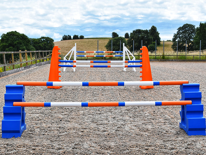 Blue MultiJumps with 9 Band Poles coloured Orange, Blue and White. Behind that, 2 orange 8 Cups with 9 band poles coloured: Blue, Orange and white. At the back White Cross wings with 9 band poles coloured Blue, white and orange. All jumps in arena.