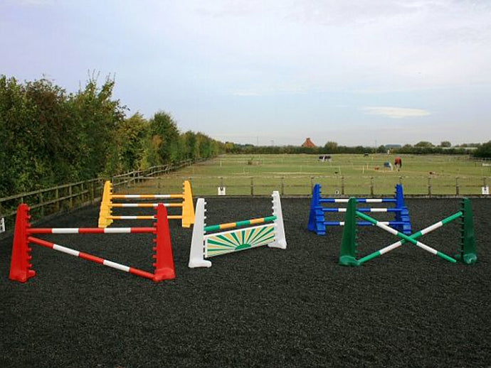 From left to right, 1 pair of red 8 cups with 2 5 band poles in red and white. 1 pair of yellow 8 Cups and yellow MultiJumps with 3 5 Band Poles. In the centre is a pair of white 8 Cups with 1 5 Band Pole in green and yellow with a green and yellow sunrise large hanging filler below it. 1 pair of blue 8 Cups and Blue MultiJumps with 3 5 Band Poles in blue and white. On the right is a pair of green 8 Cups with 2 green and white poles. All jumps in an arena.