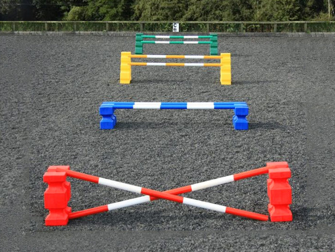4 rows of jumps. From front to back is a red pair of PolyJump Blocks with 2 5 band red and white poles. Behind that fence is the same in blue. Then a pair of yellow MultiJumps with 2 yellow and white 5 band poles. Finally a pair of green MultiJumps with green and white poles.