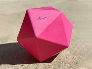 Pink Treat Ball on floor with blue PolyJumps logo facing upward.