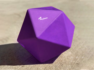 Purple Treat Ball on floor with white PolyJumps logo facing upward.