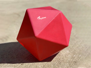 Red Treat Ball on floor with white PolyJumps logo facing upward.
