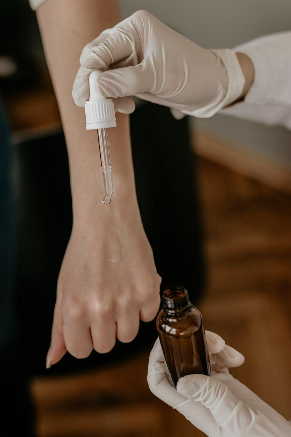 picture of a woman applying essential oils and cosmetics to another woman's hand