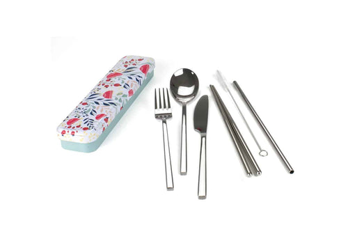 Image of personal cutlery set metal case sat next to the contents of a fork, spoon, knife, chop sticks, straw and straw cleaner. The metal case has a botanical print of blue, red and yellow on a white background on the lid, is hinged on one side and has a pale blue base.