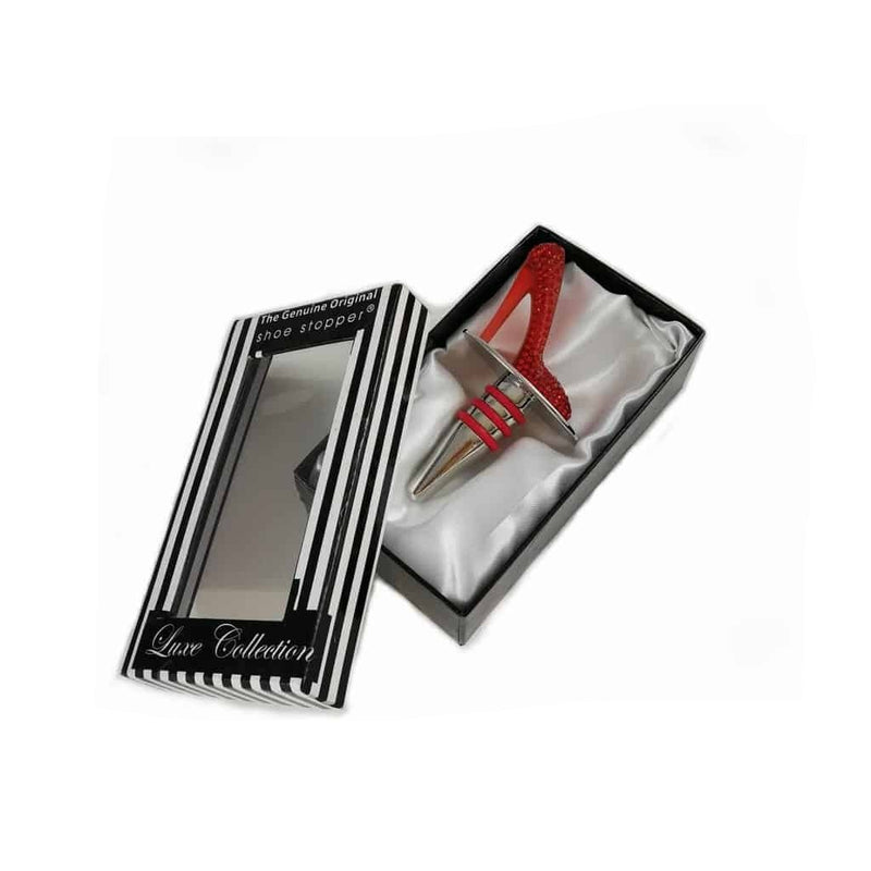 Bottle stopper in the shape of stiletto shoe, covered in red crystals, sitting in gift box which is lined with white satin.  The box is black and white striped and has a clear window on the front to show the shoe wine stopper inside.