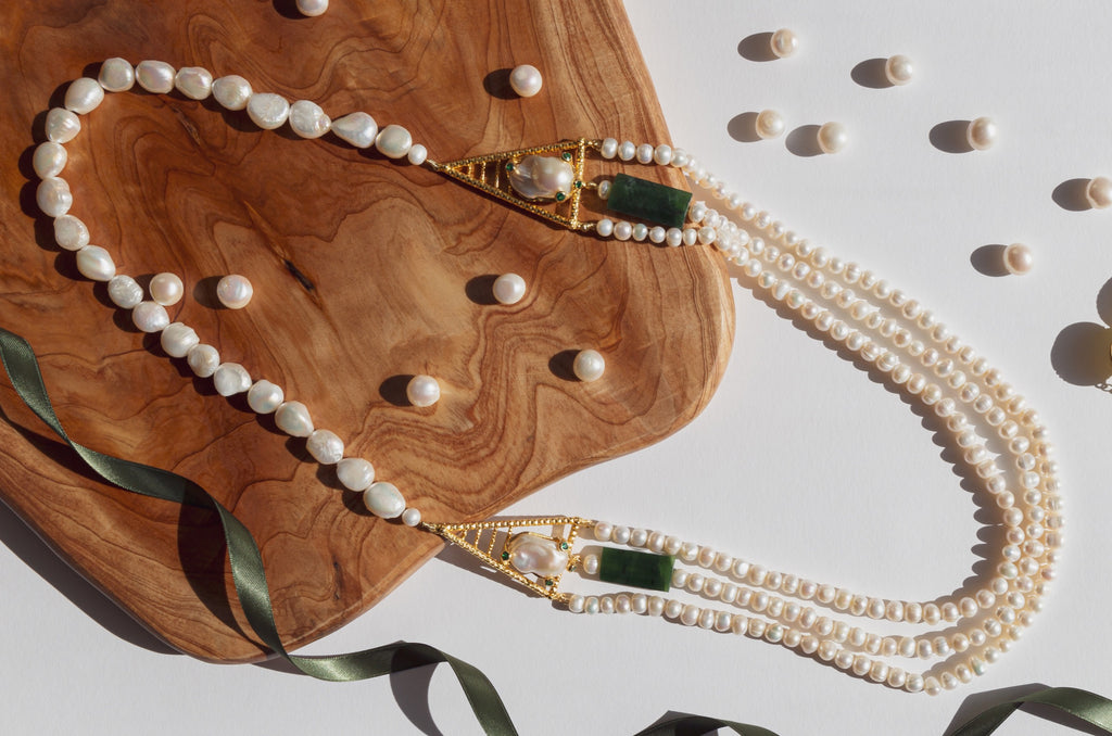 Joyful blend of historical references in its aesthetic is what makes this necklace unique. Freshwater pearls empowered with strong and significant green jade elements and gold plated silver cast that embraces the baroque pearl with a touch of four pieces of sparkling green topaz