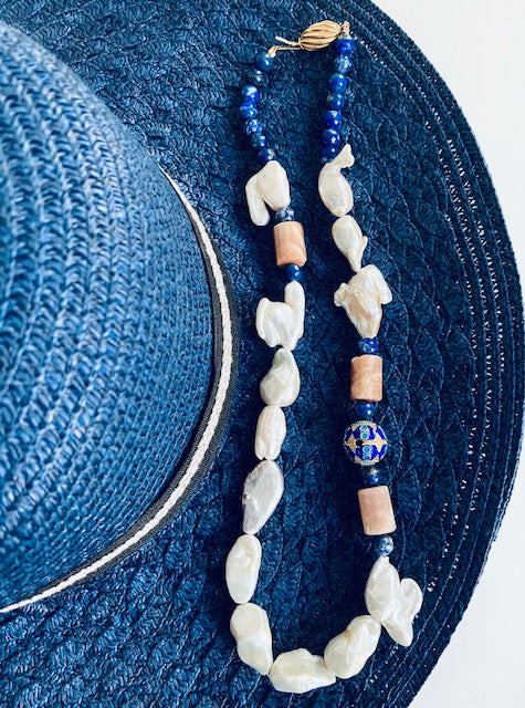 Necklace made of baroque and keishi pearls, gentle lapis lazuli, peachy chalcedony with a bold Chinese enamel and shell like clasp both in gold plated silver. Enjoy this unique rhapsody in blue