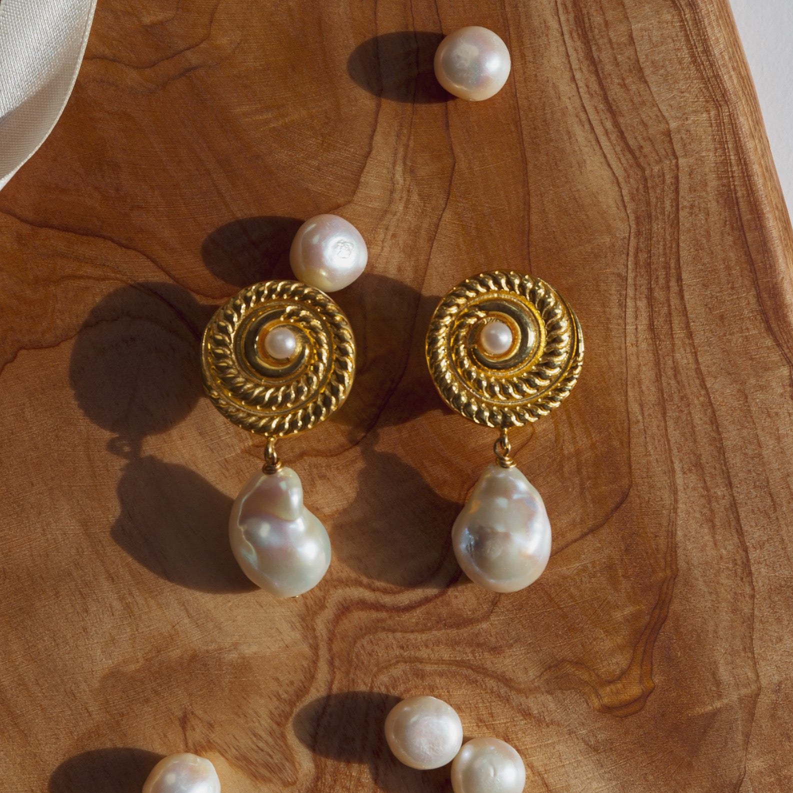 Earrings that one can wear forever. Carefully selected baroque pearls and gold plated silver round element with freshwater pearl. Our hero product